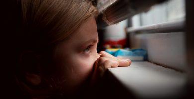 niña mirando por la ventana a través de una persiana veneciana a medida